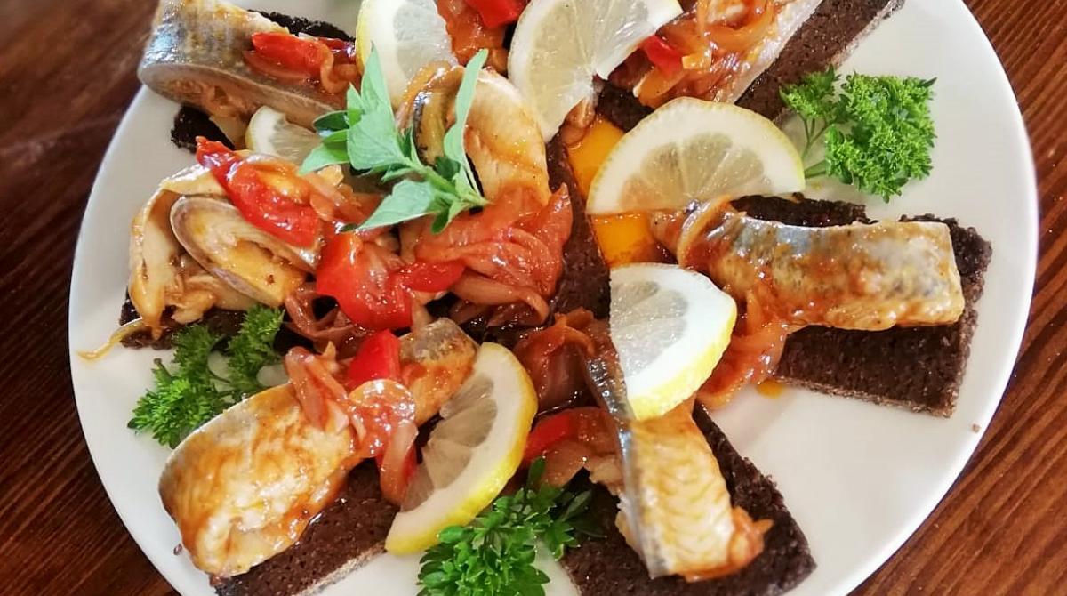 Śledź pokaszubsku zesmażoną cebulką ipomidorami podany napumperniklu restauracja Bukowa Przystań Barlinek